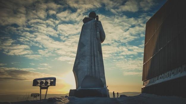 Bug giant alyosha monument, murmansk. landmark in sunset evening clouds sky