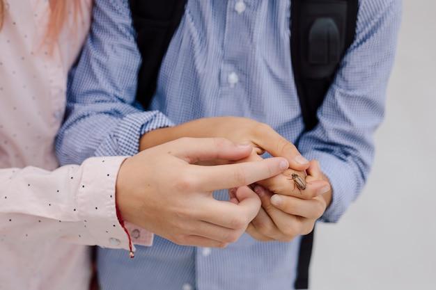 Ошибка на руках детей девочки-подростка и мальчика. экологичная концепция. фото крупным планом