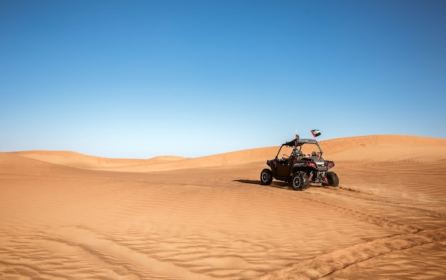 에미레이트 항공의 깃발과 흔적이 있는 두바이 사막 사파리에서 운전하는 버기 쿼드 바이크