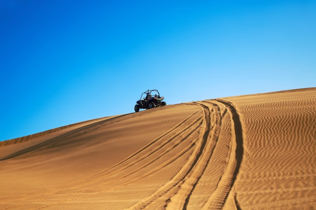 Buggy quad drive on desert sand hill and leave wheel tracks