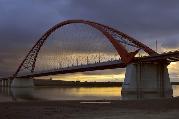 黄金の夜明けのオビ川を渡るブグリンスキー橋