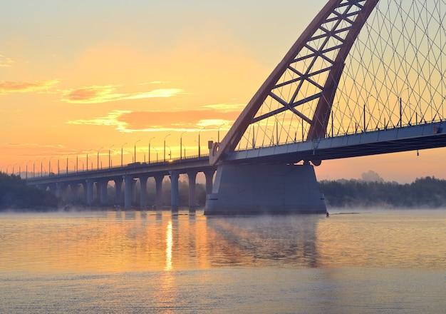 夜明けのブグリンスキー橋。朝の霧の中で大きなシベリアのオビ川に架かる自動車橋