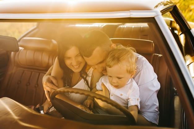 ビュイックリビエリンのレトロなスタイル。ユニークな車。かわいい金髪の少年は彼の家族とレトロな車のホイールの後ろに座っています。