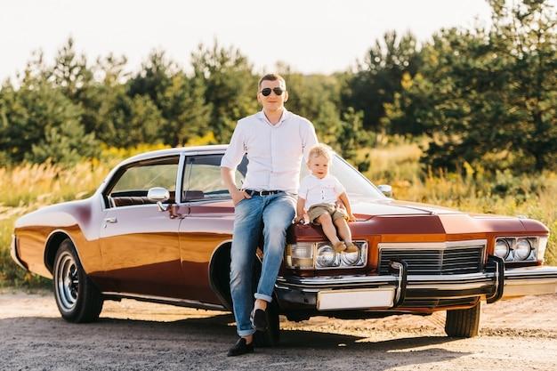 ビュイックリビエリンのレトロなスタイル。ユニークな車。お父さんと息子が夕日にレトロな車のボンネットの上に座っています。