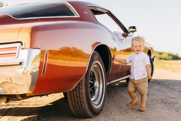 Buick rivierin в стиле ретро. уникальная машина. милый белокурый мальчик остаться возле ретро-автомобилей.