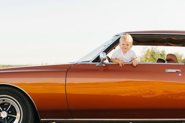 Buick rivierretro стиль. уникальная машина. милый белокурый мальчик выглядывает из окна ретро-автомобиля