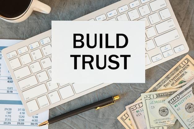 Строительство доверия записывается в документе на офисном столе с офисными принадлежностями, кофе, деньгами и клавиатурой.