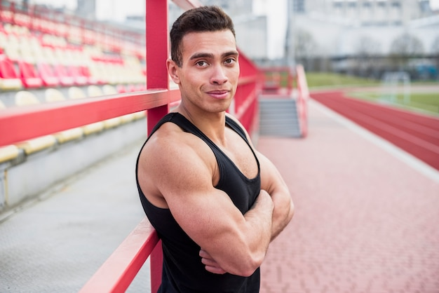 Build up athlete with his arm crossed at stadium track and field