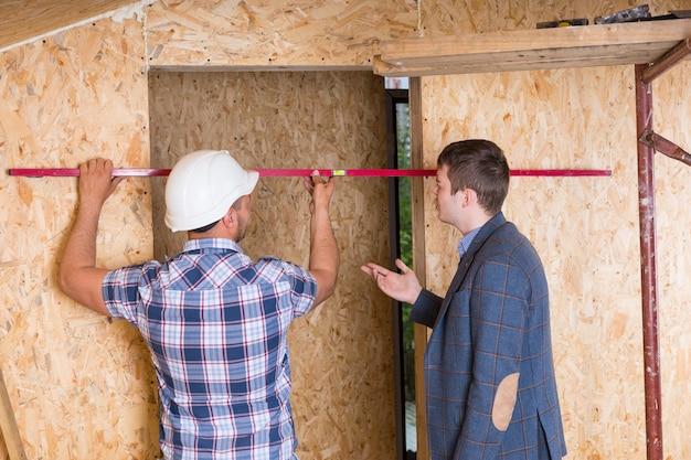 건축업자 및 건축가는 노출된 입자 합판 보드가 있는 미완성 주택 내부 수준이 있는 문틀 건설을 검사합니다.