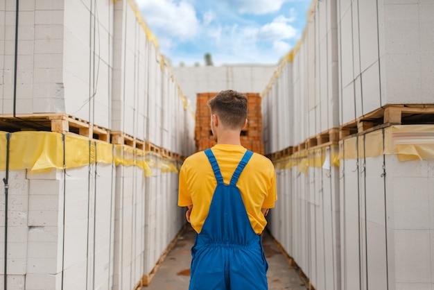 Builder between big pallets of building materials