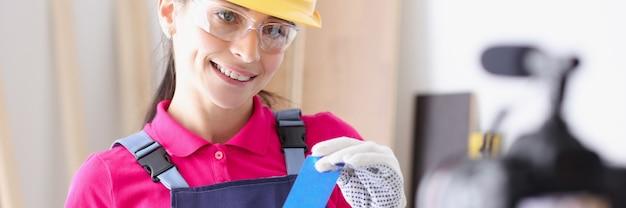 Блогер-строитель демонстрирует на камеру синюю изоленту для ремонта