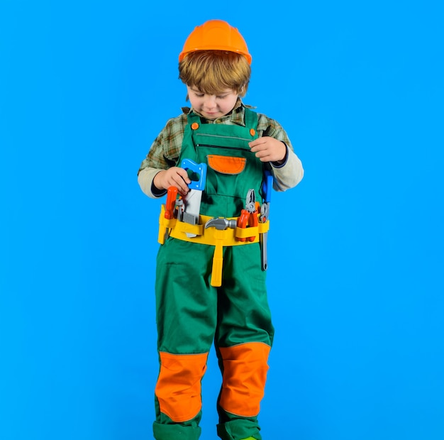 Builder boy in helmet and toolbelt little kid repairman holds saw in hand smiling toddler with tools