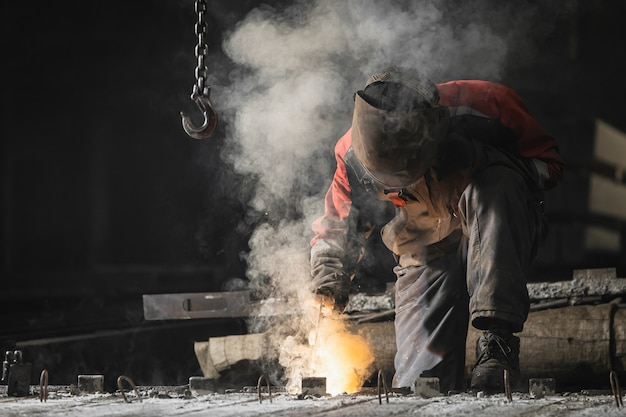 Builder in brown uniform, welding mask and welders leathers. weld metal with a arc welding machine, yellow sparks fly to the sides