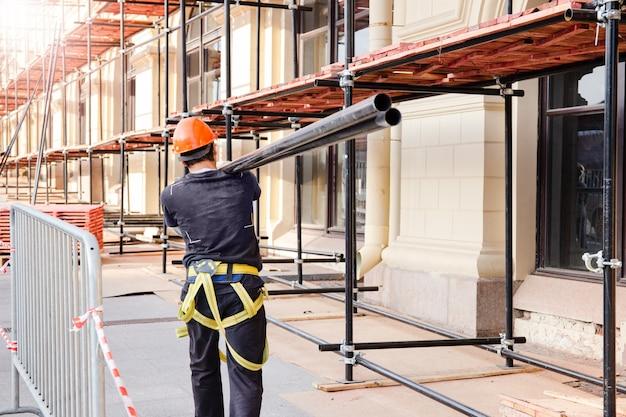 빌더는 어깨에 강철 빔을 들고 있습니다. 건설 현장, 건물 건설 및 재건축 과정.