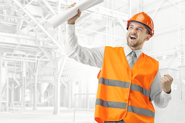 The builder in a construction vest and orange helmet smiling as winner against industrial background. safety specialist, engineer, industry, architecture, manager, occupation, businessman, job concept