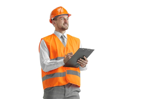 The builder in a construction vest and orange helmet standing on white studio