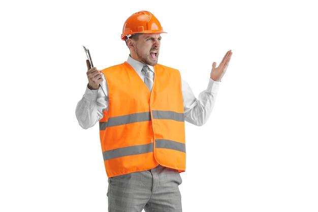 Il costruttore in un giubbotto di costruzione e casco arancione in piedi su studio bianco