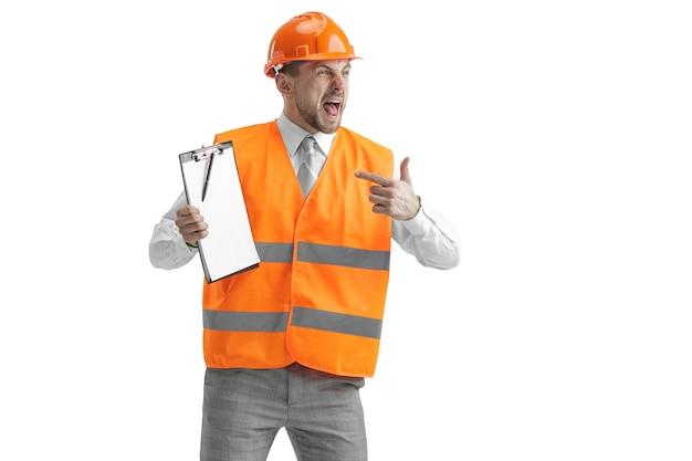 Il costruttore in un giubbotto di costruzione e casco arancione in piedi sul muro bianco. specialista della sicurezza, ingegnere, industria, architettura, manager, occupazione, uomo d'affari, concetto di lavoro