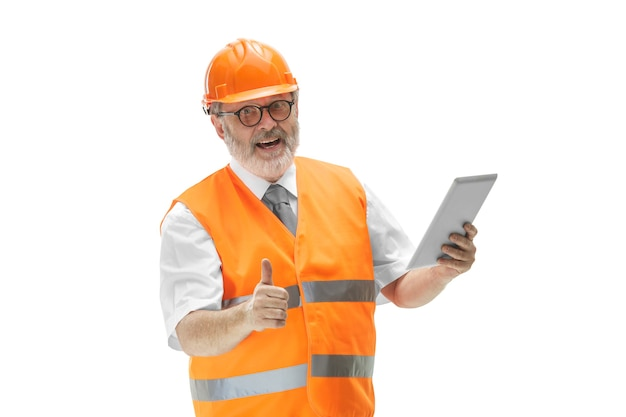 Builder in a construction vest and orange helmet standing with tablet on white background.
