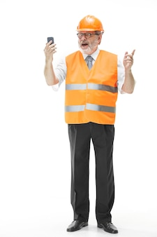 The builder in a construction vest and an orange helmet talking on a mobile phone about something.