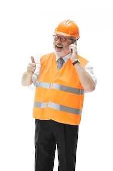 The builder in a construction vest and an orange helmet talking on a mobile phone about something