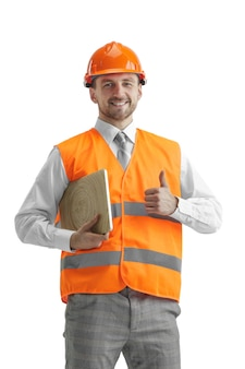 The builder in a construction vest and an orange helmet with laptop. safety specialist, engineer, industry, architecture, manager, occupation, businessman, job concept