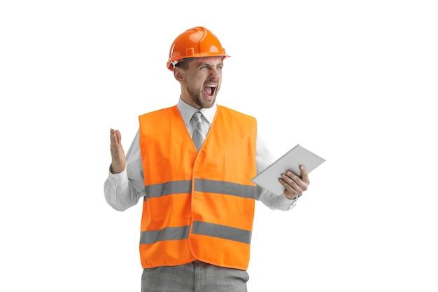 Il costruttore in un giubbotto di costruzione e un casco arancione con tablet. specialista della sicurezza, ingegnere, industria, architettura, manager, occupazione, uomo d'affari, concetto di lavoro