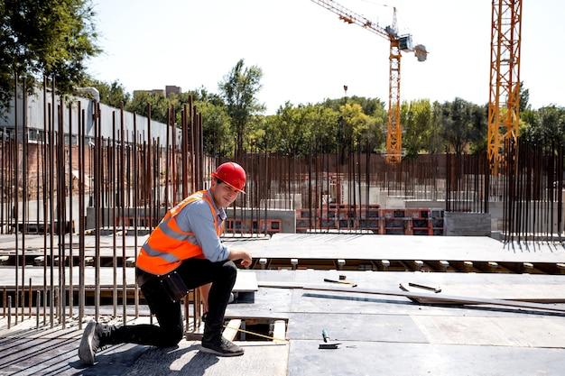 Builder dressed in orange work vest and helmet uses a tape measure on the building site . .