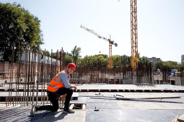 Builder dressed in orange work vest and helmet uses a tape measure on the building site .