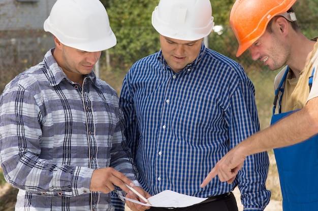 建築現場でヘルメットのドキュメントについて話し合う会議に立っているビルダー、エンジニア、建築家