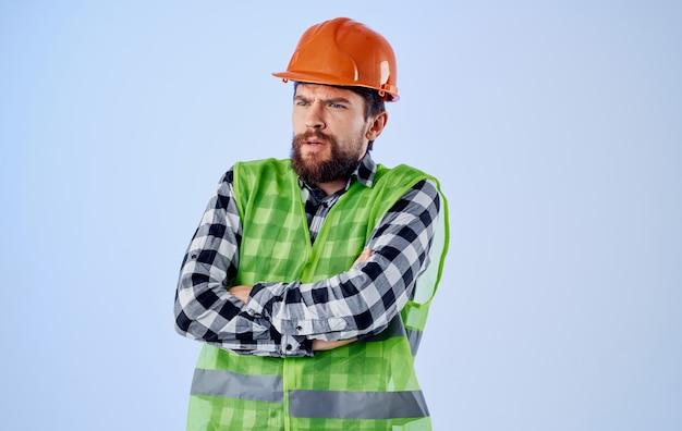 파란색 배경 및 반사 조끼에 손으로 몸짓 하드 모자에 작성기 엔지니어. 고품질 사진