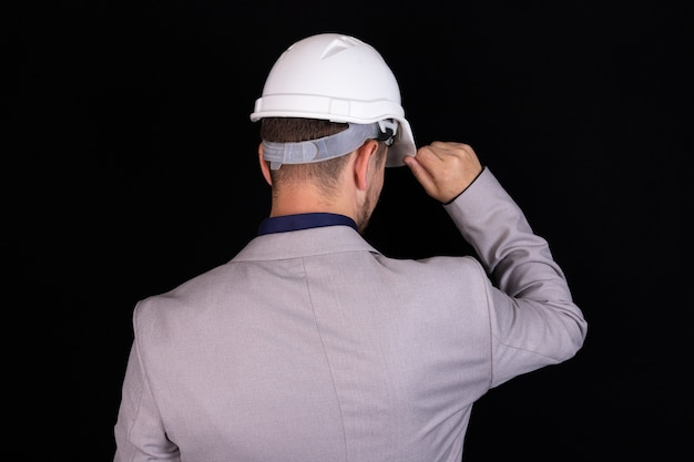 A builder engineer stands with his back with a white hard hat on black