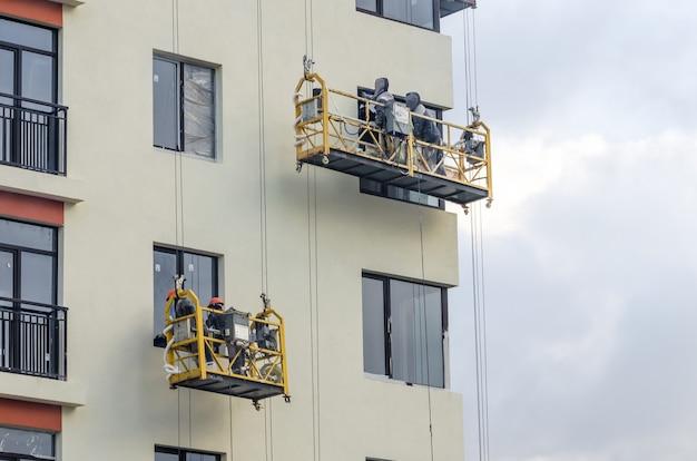 Builder at facade construction work hanging cradles.