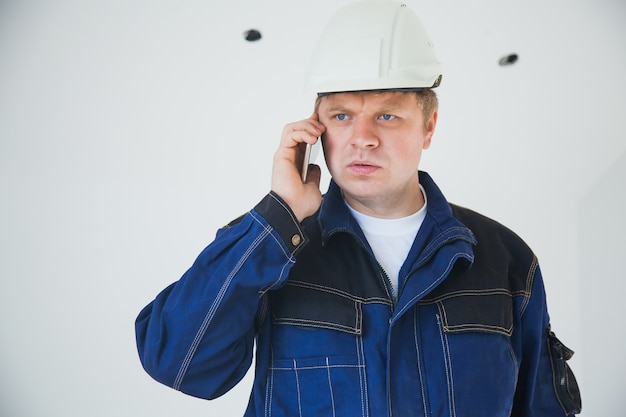 屋内の建設現場で白いヘルメットをかぶったビルダーの職長、フラットな改修のコンセプト、スマートフォンで話している職場のプロの職長