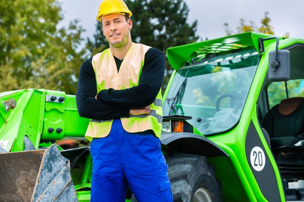 Builder in front of  construction machinery