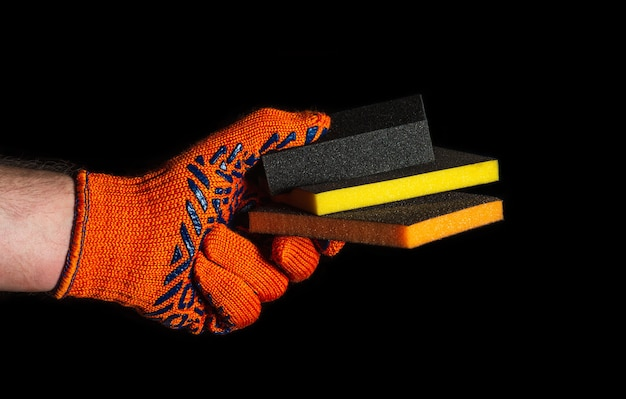 Рука строителя в перчатке держит или дает абразивные инструменты крупным планом на изолированном черном фоне. идея начать успешную работу. бесплатное рекламное место.