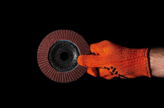 Рука строителя в перчатке держит или дает крупным планом абразивные инструменты на изолированном черном фоне