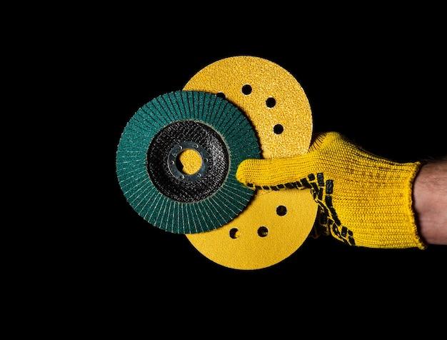Рука строителя в желтой перчатке держит или дает абразивные инструменты крупным планом на изолированном черном фоне