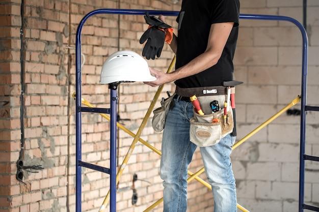 Строитель разнорабочий со строительными инструментами. дом и концепция ремонта дома.