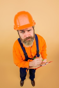 Builder in hard hat engineer making notes man in overalls construction worker holds folder serious