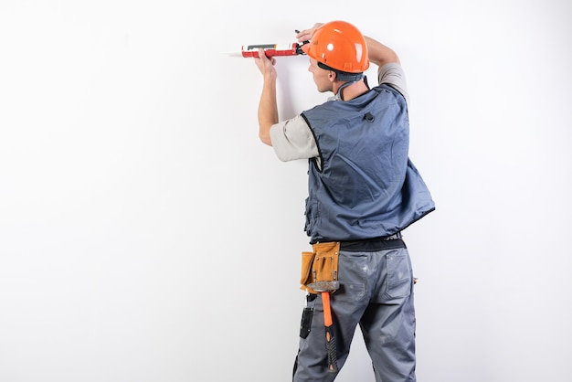 A builder in a helmet, with silicone in a mounting gun, aims at the frame. for any purpose.