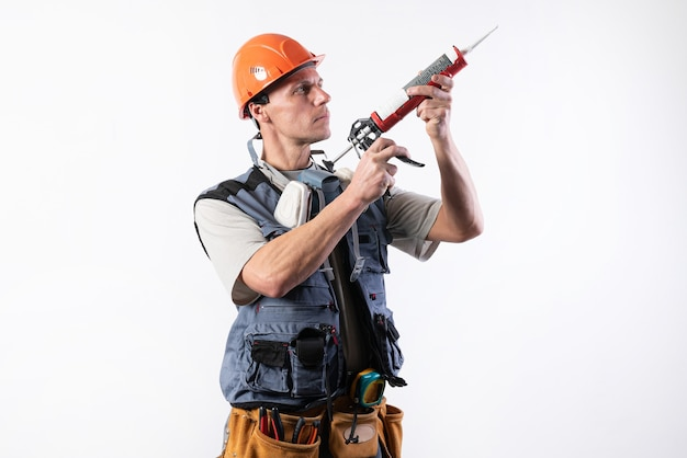 A builder in a helmet, with silicone in a mounting gun. holds in hands. on a light background. for any purpose.