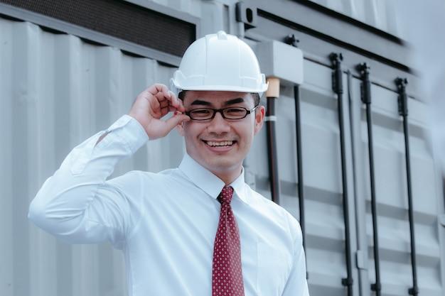 建設現場で建築図面計画を紙に保持し、ヘルメットをかぶっているビルダー。