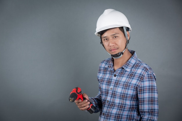 Builder holding drill on grey background