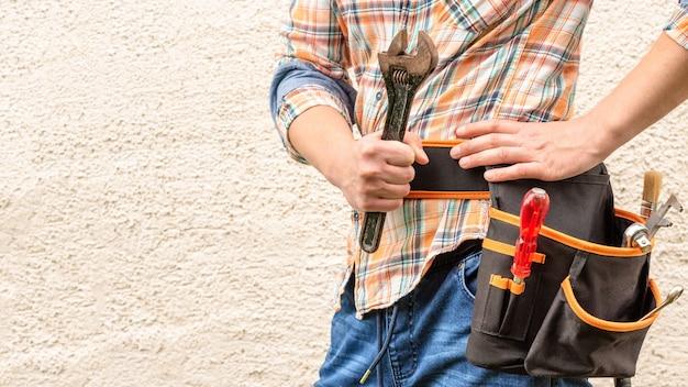 Строитель держит в руке большой разводной ключ.