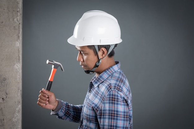 The builder holds a hammer on the plaster wall on a gray background