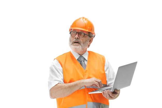 Строитель в жилете строительства и оранжевом шлеме с ноутбуком.