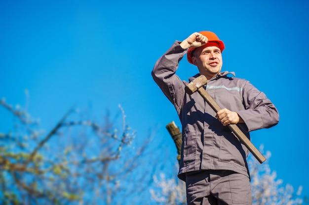 Строитель в оранжевой каске с кувалдой в руках.