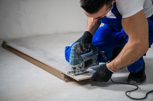 Строитель в синей спецодежде распиливает ламинатные доски электрической пилой