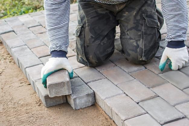 Строитель в перчатках кладет брусчатку на дорогу. мощение дорог, строительство, ремонт тротуаров.